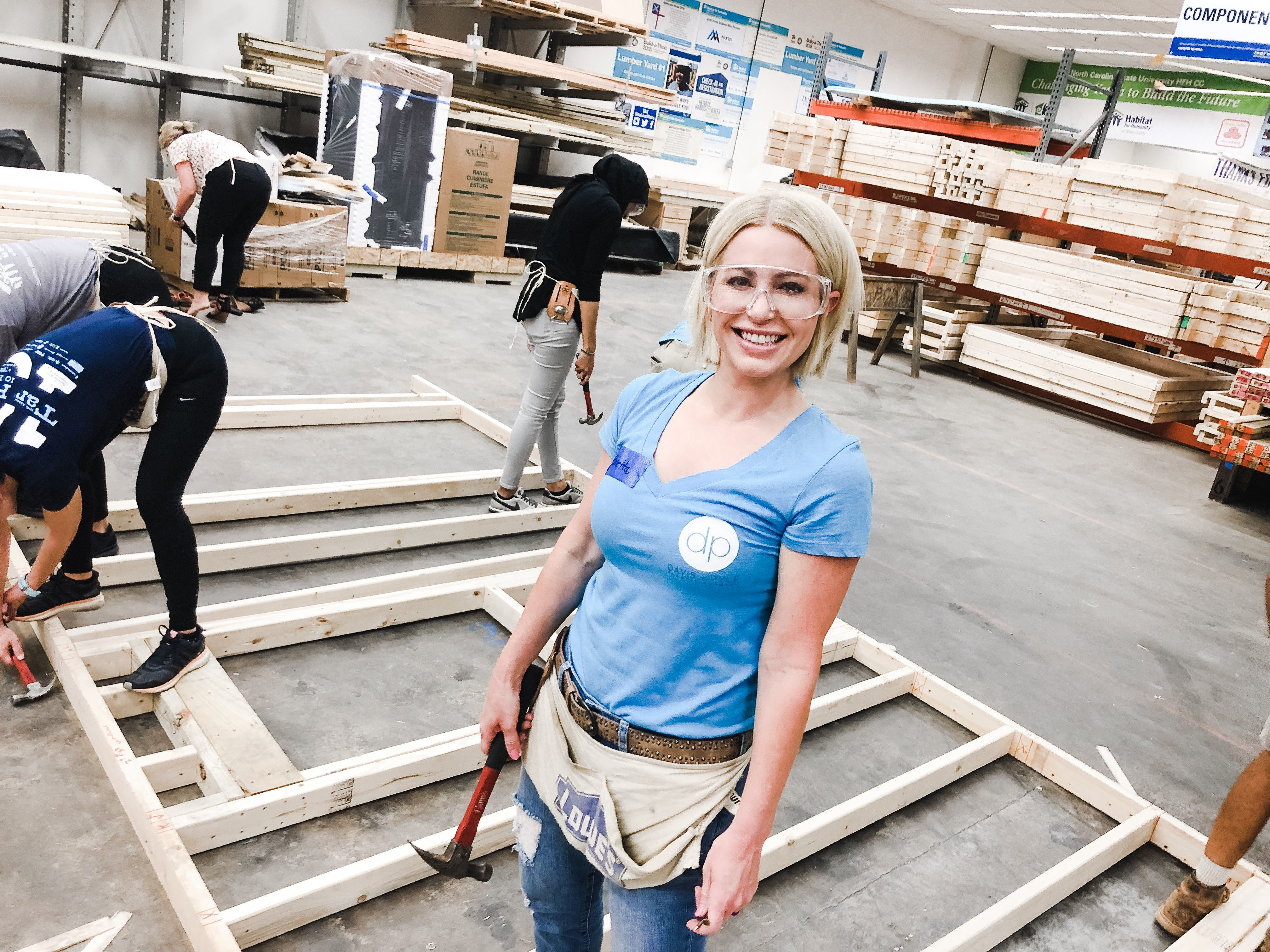 Habitat Wake Women Build board chair in the warehouse with a hammer