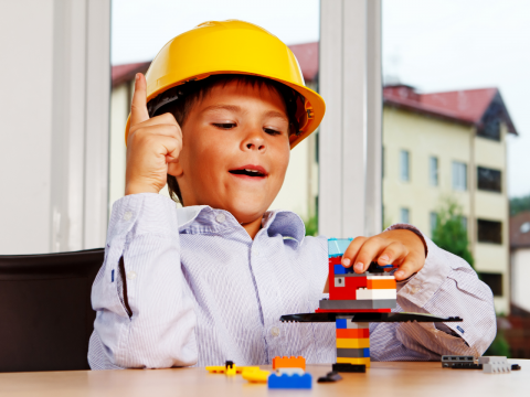 Child wearing hard hat building with Legos