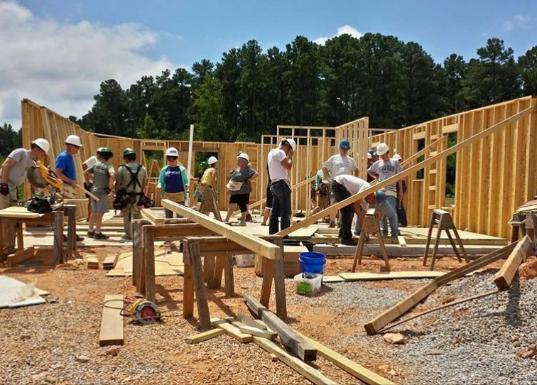 Volunteers on the construction site framing a Habitat Wake home.