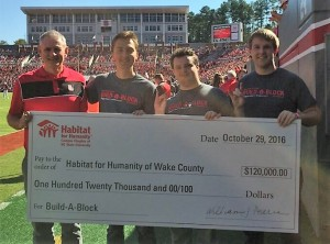 Kevin Campbell joined Habitat Chapter at NC State leaders Parker Colbath, Tripp Pearce, and Alexander Simpson during halftime of NC State's Homecoming game to accept the group's contribution to Build-A-Block.